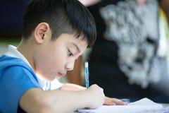 Giovane ragazzo asiatico che fa il suo compito Fotografia Stock Libera da Diritti
