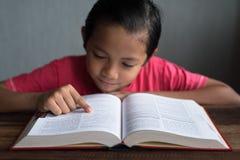 Giovane ragazzo asiatico che legge un libro Fotografie Stock