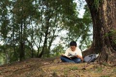 Giovane ragazzo asiatico che legge un libro sotto un albero in un parco Fotografia Stock