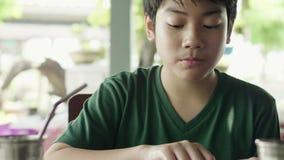 Giovane ragazzo asiatico che mangia riso fritto con carne per la prima colazione stock footage