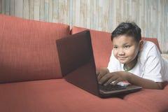 Giovane ragazzo asiatico che per mezzo del computer portatile su un sofà a casa Fotografie Stock