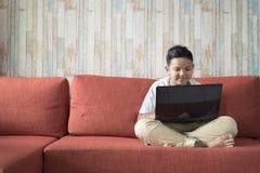 Giovane ragazzo asiatico che per mezzo del computer portatile su un sofà a casa Immagine Stock