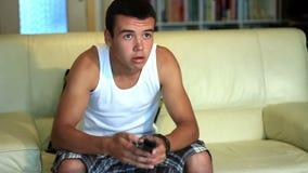 Giovane ragazzo attraente dell'adolescente che salta sul sofà stock footage