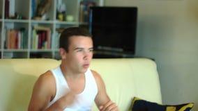 Giovane ragazzo attraente dell'adolescente che salta sul watc del sofà stock footage