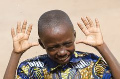 Giovane ragazzo bello che mostra le mani che ridono all'aperto fotografie stock