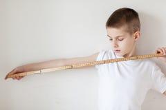 Giovane ragazzo bianco bello che tiene un bastone del tester Immagine Stock