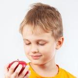 Giovane ragazzo in camicia arancio con la mela rossa Fotografie Stock