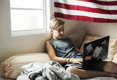 Giovane ragazzo caucasico che si trova facendo uso del computer portatile del computer sul letto Fotografie Stock Libere da Diritti