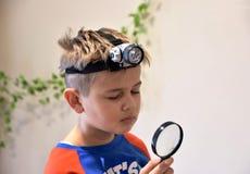Giovane ragazzo caucasico con la lampada capa della torcia che guarda attraverso un vetro della lente Fotografia Stock Libera da Diritti