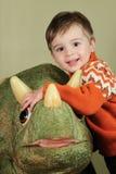 Giovane ragazzo che abbraccia dinosauro Fotografia Stock Libera da Diritti