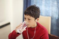 Giovane ragazzo che beve da un bicchiere d'acqua Fotografie Stock Libere da Diritti