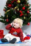 Giovane ragazzo che comunica sul telefono mobile sotto un albero di Natale. Fotografia Stock Libera da Diritti