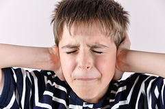 Giovane ragazzo che copre le sue orecchie di mani Fotografia Stock Libera da Diritti