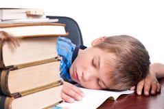 Giovane ragazzo che dorme sul suo scrittorio Fotografie Stock Libere da Diritti