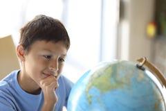 Giovane ragazzo che esamina un globo Fotografie Stock