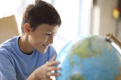 Giovane ragazzo che esamina un globo Fotografia Stock Libera da Diritti