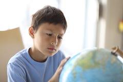 Giovane ragazzo che esamina un globo Fotografie Stock Libere da Diritti