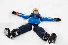 Giovane ragazzo che fa angelo della neve sul pendio Fotografie Stock Libere da Diritti