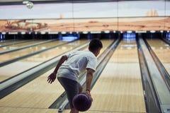 Giovane ragazzo che gioca bowling fotografia stock libera da diritti
