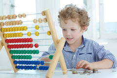 Giovane ragazzo che gioca con il contatore e le monete Fotografia Stock Libera da Diritti