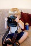 Giovane ragazzo che gioca con la macchina fotografica digitale di SLR immagine stock libera da diritti
