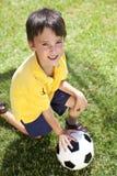 Giovane ragazzo che gioca con la sfera di calcio o di gioco del calcio Immagine Stock Libera da Diritti