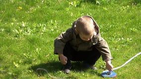 Giovane ragazzo che gioca con nastro adesivo di misurazione nel cortile 02 archivi video