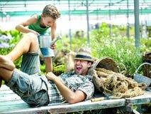 Giovane ragazzo che gioca con suo padre in una serra Immagini Stock