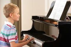 Giovane ragazzo che gioca grande piano Fotografia Stock