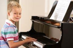 Giovane ragazzo che gioca grande piano nel paese Fotografia Stock Libera da Diritti