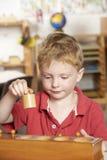 Giovane ragazzo che gioca a Montessori/addestramento preliminare Fotografia Stock