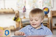 Giovane ragazzo che gioca a Montessori/addestramento preliminare Fotografia Stock Libera da Diritti