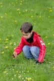 Giovane ragazzo che gioca nell'erba immagini stock libere da diritti