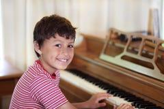 Giovane ragazzo che gioca piano Fotografia Stock Libera da Diritti