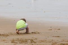 Giovane ragazzo che gioca su una spiaggia sabbiosa Fotografie Stock Libere da Diritti