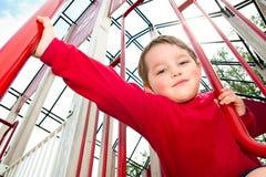 Giovane ragazzo che gioca sul campo da giuoco Fotografie Stock