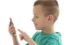 Giovane ragazzo che gioca sulla cellula fotografia stock
