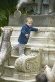 Giovane ragazzo che gioca sulla statua in parco, Parigi, Francia Immagine Stock