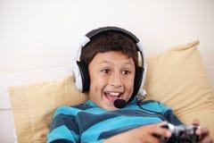 Giovane ragazzo che gioca video gioco con i suoi amici Immagine Stock