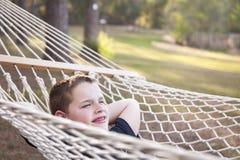 Giovane ragazzo che gode di un giorno in sua amaca fotografie stock libere da diritti