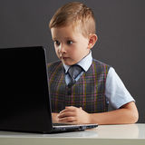 Giovane ragazzo che guarda nello schermo del taccuino Bambino divertente con il computer Fotografia Stock Libera da Diritti