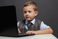 Giovane ragazzo che guarda nello schermo del taccuino Bambino divertente con il computer Immagini Stock Libere da Diritti