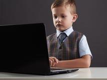 Giovane ragazzo che guarda nello schermo del taccuino Bambino divertente con il computer Fotografie Stock Libere da Diritti