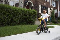 Giovane ragazzo che guida la sua bicicletta Immagine Stock