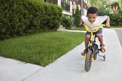 Giovane ragazzo che guida la sua bicicletta Fotografie Stock Libere da Diritti