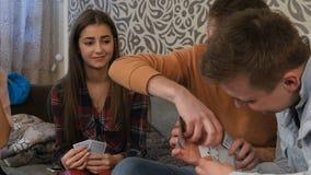 Giovane ragazzo che imbroglia in gioco del poker con gli amici, rimuoventi le carte da gioco dalla manica immagine stock libera da diritti