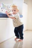 Giovane ragazzo che impara camminare tenendo sulla mobilia Fotografia Stock Libera da Diritti