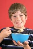 Giovane ragazzo che mangia cereale vertic fotografia stock