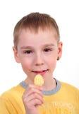 Giovane ragazzo che mangia le patatine fritte Fotografie Stock