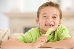 Giovane ragazzo che mangia sedano in salone immagine stock